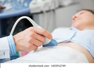 Sonographer using ultrasound machine at work. Modern clinical diagnostics and treatment. Close-up ultrasound scanner in hand of doctor. Doctor ultrasound examine female patient abdomen at hospital.