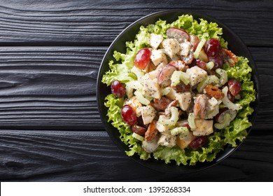 Sonoma salad with chicken breast, celery, pecans and grapes seasoned with spicy sauce close-up on a plate on the table. Horizontal top view from above