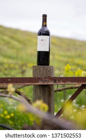 Sonoma Valley, CA - April 4, 2019: Acorn Hill red blend wine on the top of a vineyard support post with wildflowers in bloom along the grape vines in early Spring.