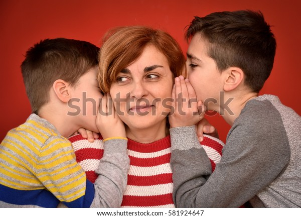 Sons whispering secret into ears of smiling mother