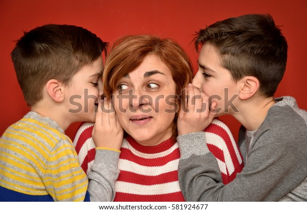 Sons whispering secret into ears of surprised mother