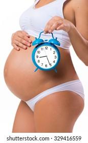Soon birth. Pregnant belly with alarm clock. Conceptual image of happy pregnancy.