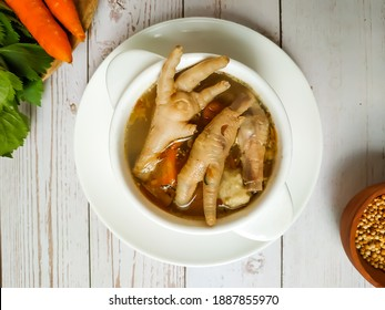SOp Ceker Ayam or Clear Chicken Feet (Claw) Soup. Served on white wooden Table in white Bowl. Selective focus blurry background. Top view. Copy space for text