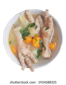 Sop ceker or chicken feet soup in a white bowl isolated on white background. Indonesian chicken feet soup with carrot, cabbage, and celery. Chicken feet and vegetable soup in a white bowl