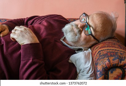 Sophisticated bearded old man sleeping on sofa at home. Elderly man felt asleep on sofa. Ill grandfather having rest at living room. Health care / Healthcare concept.