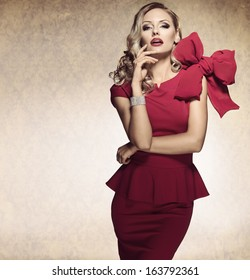 sophisticated elegant lady in red dress with a big bow and jewellery looking in camera with arrogant expression