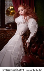 A sophisticated fashion model girl with lush red hair with fine curls poses in a vintage interior in art dress with a ruffled renaissance collar. History of fashion and hairstyles.