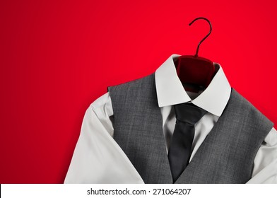 Sophisticated mans white shirt, grey waistcoat and tie on clothes hanger in bottom right corner on red background.