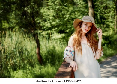 A sophisticated red-haired girl in a simple linen dress, in a light wide-brimmed hat. Model look. Natural beauty. Artistic portrait