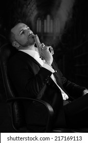 Sophisticated young man agent police killer hitman assassin sitting in a chair holding a gun against his lips black and white portrait