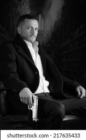 Sophisticated young man agent police killer hitman assassin sitting in a chair holding a gun over dark background black and white portrait