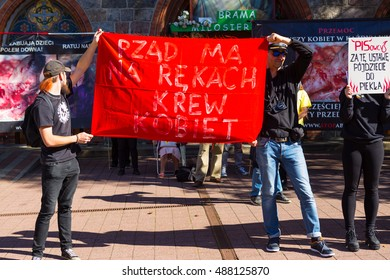 Sopot, Poland, 2016 09 24 - protest against anti-abortion law forced by Polish government; people with banner: government have blood of women on hands, trying to cover banners of pro-life protesters
