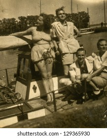 SOPOT, POLAND - CIRCA 1949: vintage photo of group of unidentified young people - one of them is a woman in bathing suit, circa 1949 in Sopot, Poland