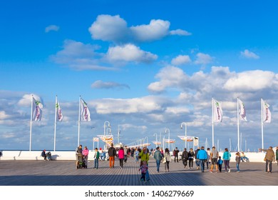 Sopot, Poland - July 31, 2015: Tourists walking on a pier (Molo) in Sopot city, Poland. Built in 1827 with 511m long it is the longest wooden pier in Europe