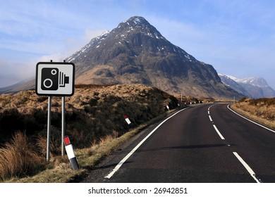 A sopped camera warning sign by the roadside near Glencoe, Scotland