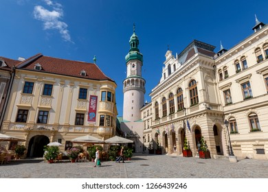 Sopron, Hungary - Jun 2 2018: People are basking under the summer sun at the Main Square coffee. Background view of famous Fire Tower.