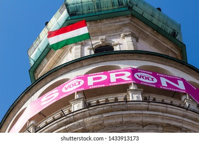 Sopron / Hungary - June 24 2019: Pink Telekom banner of Volt Festival fixed on Firewatch Tower. Close-up with Hungarian flag.