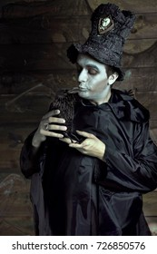 The sorcerer in the scenery of Halloween in a hat with a crow
