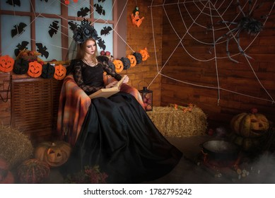 the sorceress sits in a chair and reads a magic book. A large spider is sitting on the wall on a web, and a potion is being brewed in a cauldron. The witch is waiting for the holiday of Halloween.