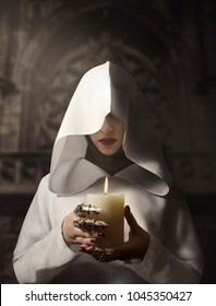 Sorceress in white hooded cloak holding a burning candle standing in the castle.