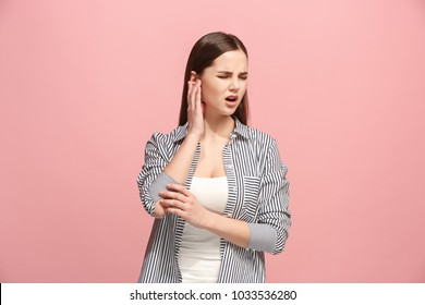 Sore ear. Ear ache concept. The sad crying woman with headache or pain on trendy pink studio background. Facial expressions and people emotions concept. Front view. Half-length portrait. Young woman.