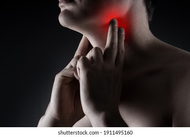 Sore throat, men with pain in neck on black background, painful area highlighted in red