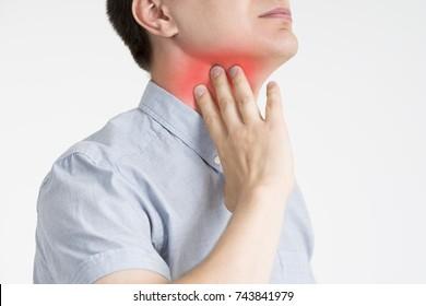 Sore throat, men with pain in neck, gray background, studio shot
