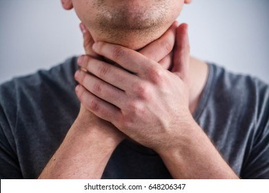 Sore throat. Men touching the neck