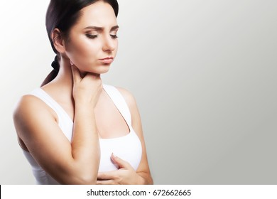 Sore throat. Sick woman, flu Young beautiful woman with sore throat. Feeling painful in the throat. The concept of health. On a gray background.