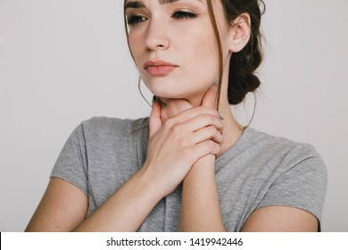 Sore throat. Woman holding hands on her throat. Heartburn concept.
