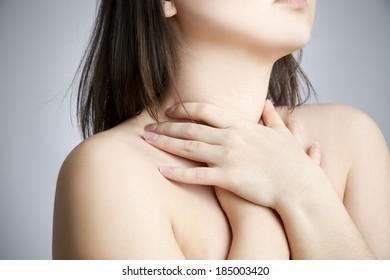 Sore throat of a women. Touching the neck.