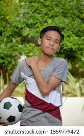 Sore Young Filipino Male Soccer Player With Soccer Ball