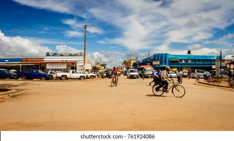 SOROTI, UGANDA – NOVEMBER 04, 2017: Typical street life in Soroti Uganda with its famous rock in the background. Many bicycles and a few cars showing an easy going African town.