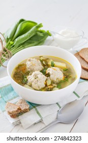 Sorrel soup with meat balls in white bowl, sour cream, plaid napkin, white wood background