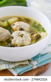 Sorrel soup with meat balls in white bowl, sour cream, plaid napkin, white wood background, closeup