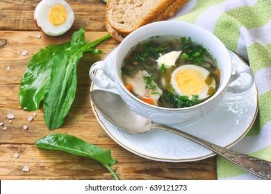 Sorrel soup in a white bowl, salt, towel, boiled egg, leaves, bread on a wooden table