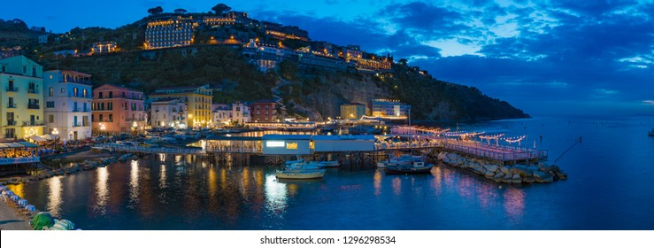 Sorrento, Italy - May 01, 2018: Panoramic night view of Marina grande in Sorrento - popular travel destination in Italy. Illuminated streets of city are reflected in sea.