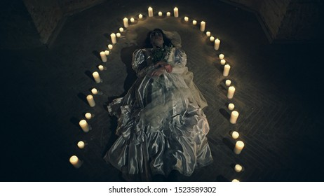Sorrow scene of a corpse bride on the floor like a ritual with candles