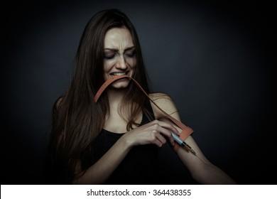 Sorrow young girl going to use a drug syringe