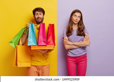Sorrowful dissatisfied man overloaded with colorful shoppings bags, feels tired of walking long hours on different shops, indifferent woman keeps hands crossed, doesnt help husband carry package