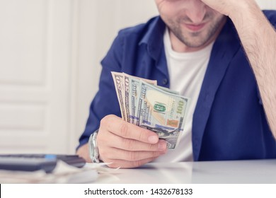 Sorrowful man getting stressed over finances, does not have enough money for all his debts, bills and calculator on the table, cropped image, close up, toned