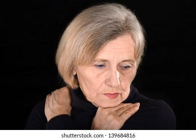 sorrowful senior woman thinking on a black background
