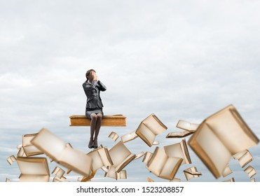 Sorrowful woman sitting on big book and flying in blue sky. Shocked girl in business suit keeps hands on face. Businesswoman in despair on background of cloudscape panorama with open books