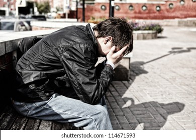 sorrowful young man sitting on the city street