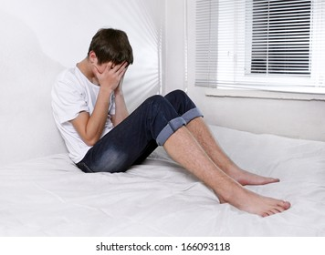 Sorrowful Young Man sitting on the bed Alone
