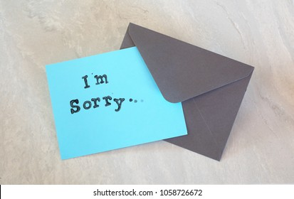 I'm Sorry Apology Words Stamped in Black on Teal Card with a Dark Gray Envelope on Gray Marble Table.  It's a horizontal with a flat layout, above-view angle.  Room or space on sides for copy or text.