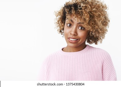 Sorry but. African-american woman feeling awkward as hinting friend at flaw, making apologizing smile raising eyebrows and looking at camera doubtful and hesitant, unsure over white wall