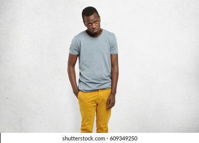 I'm so sorry. Cropped portrait of attractive African male in casual t-shirt and mustard pants, looking at camera with guilty expression, apologizing and asking to forgive him for making mistake