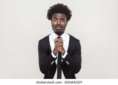 Sorry, hope concept. African businessman looking at camera and apologize. Studio shot, gray background