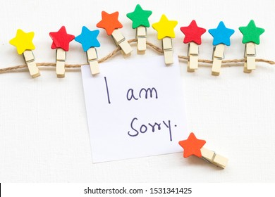 i am sorry message card handwriting with colorful wooden star clips arrangement flat lay postcard style on background white
